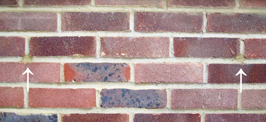 Brick wall with 2 small drill holes which have been filled